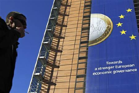 A banner featuring a Euro coin is seen on the European Commission headquarters building ahead of a European Union heads of state summit in Brussels October 26, 2011. REUTERS/Yves Herman/Files