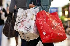 Женщина несет покупки в магазине в Северной Калифорнии, 25 ноября 2011 года. Продажи американских ритейлеров в минувшие выходные Дня Благодарения выросли на 16,4 процента в годовом выражении до рекордных $52,4 миллиарда благодаря перенесению часов начала торговли и привлекательным акциям, завлекшим в магазины большее число покупателей, сообщила Национальная федерация розничной торговли.  REUTERS/Chris Keane