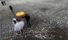 Новобрачные гуляют по Красной Площади в Москве, 11 ноября 2011 года. Легкие морозы по ночам, температура около нуля в светлое время суток и небольшие осадки ждут москвичей в течение наступившей рабочей недели, ожидают синоптики. REUTERS/Anton Golubev
