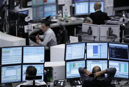 Traders work at their desks at the Frankfurt stock exchange November 15, 2011. REUTERS/Alex Domanski