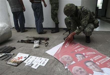 A soldier looks at election campaign posters of Fausto Vallejo from the Institutional Revolutionary Party (PRI) for the position of Michoacan governor after the arrest of suspected members of the Caballeros Templarios, a new spin-off cartel in Michoacan state linked to the Gulf Cartel, in Morelia November 11, 2011.   REUTERS/Leovigildo Gonzalez