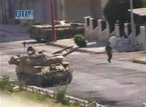 Кадр видеозаписи, на котором виден танк и солдат сирйиской армии в городе Хама 7 августа 2011 года. Рейтер не может подтвердить подлиннсоть видеоматериалов. Комиссия ООН, занимающаяся расследованием ситуации в Сирии, признала военных и силы безопасности страны виновными в преступлениях против человечности, включая убийства, пытки и изнасилования, ответственность за которые должно нести правительство Башара аль-Асада. REUTERS/Social media website via Reuters TV