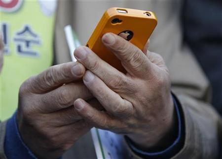 A man uses his iPhone 4 in Seoul October 25, 2011. REUTERS/Jo Yong-Hak