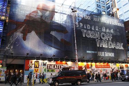 Pedestrians walk underneath a banner advertising the Broadway play ''Spiderman: Turn Off The Dark'' in New York December 23, 2010. REUTERS/Lucas Jackson