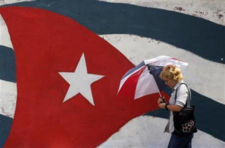 A woman walks past a mural depicting the Cuban flag in Havana, September 27, 2010. REUTERS/Enrique De La Osa