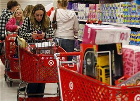 A woman uses her smartphone as she waits in line to checkout at a Target store on the shopping day dubbed ''Black Friday'' in Torrington, Connecticut, November 25, 2011. REUTERS/Jessica Rinaldi