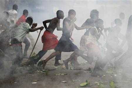 Opposition UDPS supporters run through a cloud of teargas outside N'Djili airport in Kinshasa, November 26, 2011. REUTERS/Finbarr O'Reilly