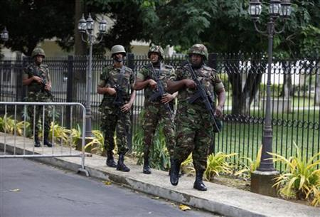 Trinidad and Tobago soldiers patrol the residence of Prime Minister Kamla Persad-Bissessar after her news conference regarding what she called an assassination plot against her, in Port of Spain November 24, 2011.    REUTERS/Andrea De Silva