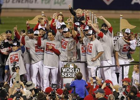 St. Louis Cardinals players celebrate wth the World Series trophy after they defeated the Texas Rangers in Game 7 to win MLB's World Series baseball championship in St. Louis, Missouri, October 28, 2011.