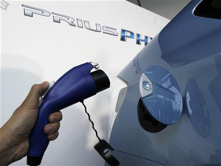 A Toyota staff holds a charger next to a Prius PHV during a photo session in Tokyo November 29, 2011. REUTERS/Kim Kyung-Hoon