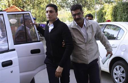 Central Bureau of Investigation (CBI) officials escort Shahid Balwa (C, in black) at the CBI headquarters in New Delhi February 9, 2011. REUTERS/Stringer/Files