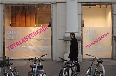 A man walks by a shop of bankrupt fashion trade chain Don Gil in Vienna, November 17, 2011. The signs read: ''Everything -50%; total sale''. REUTERS/Heinz-Peter Bader
