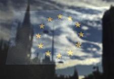 Флаг ЕС в окне, в котором отражается улица Лондона, 26 октября 2011 г.  Стремление банков избавиться от избыточной долговой нагрузки ради повышения уровня капитализации может затруднить доступ на рынок суверенного долга или привести к кредитному сжатию в экономике, свидетельствует доклад, подготовленный ко встрече министров финансов Европейского союза. REUTERS/Luke MacGregor