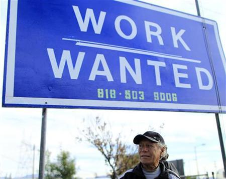 A man stands under a sign at a day laborer site in Los Angeles, California November 23, 2011. REUTERS/Lucy Nicholson