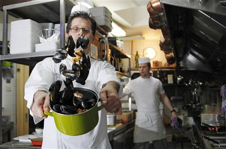 Cook Lavdim Kelmendi shakes a pot of mussels at the Volle Gas restaurant in Brussels November 24, 2011.  REUTERS/Francois Lenoir
