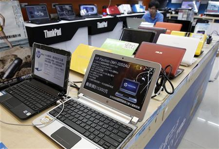 A shop attendant sits behind laptops at a computer mall in Taipei August 31, 2011.  REUTERS/Pichi Chuang