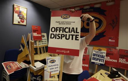 Public and Commercial Services Union (PCS) organiser Alan Brown staples a an official dispute placard together at their headquarters in Edinburgh, Scotland November 29, 2011. REUTERS/David Moir