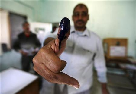 A man shows his ink stained finger after casting his vote at a polling station during parliamentary elections in Cairo November 28, 2011. REUTERS/Amr Abdallah Dalsh