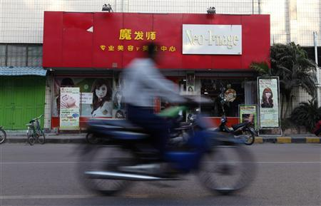 A man rides his motorbike in front of a Chinese beauty salon in Mandalay November 29, 2011.  REUTERS/Soe Zeya Tun