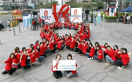 Volunteers form the shape of a giant red ribbon to show their support ahead of World AIDS Day, in front of the landmark Taipei 101 LOVE sculpture November 30, 2011.  REUTERS/Sheng-fa Lin