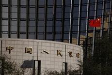 Государственный флаг Китая перед зданием Народного банка Китая в Пекине, 30 ноября 2011 г. Центральный банк Китая в среду впервые за почти три года понизил резервные требования к банкам на 50 базисных пунктов для поддержки второй по величине экономики мира. REUTERS/Zheyang SooHoo