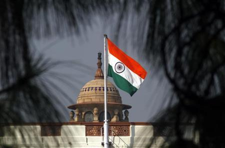 An Indian national flag flutters on top of the Indian parliament building in New Delhi December 1, 2010.  REUTERS/B Mathur