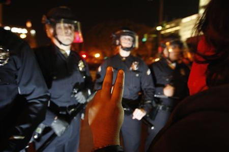 A woman makes a peace gesture during a police raid of the Occupy Los Angeles encampment at City Hall Park in Los Angeles, California November 30, 2011.  REUTERS/David McNew