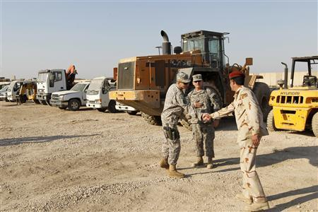 An Iraqi soldier shakes hands with a U.S. soldier at Camp Echo in Diwaniya, south of the capital Baghdad, November 27, 2011.   REUTERS/Mohammed Ameen