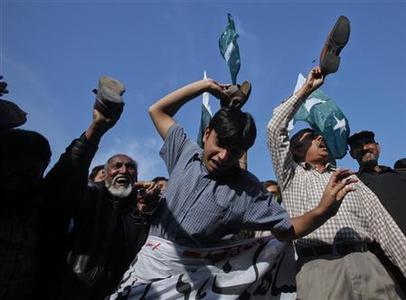 Residents, including shopkeepers and businessmen, hit the ground with their sandals to express their anger while shouting anti-American slogans during a demonstration in Lahore November 30, 2011.   REUTERS/Mohsin Raza