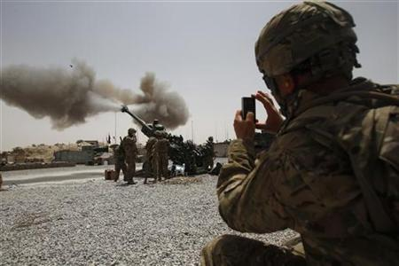 A U.S. Army soldier from the 2nd Platoon, B battery 2-8 field artillery, takes a picture of a howitzer artillery piece being fired at Seprwan Ghar Forward fire base in Panjwai district, Kandahar province in southern Afghanistan, June 12, 2011. REUTERS/Baz Ratner