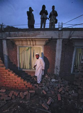 Photographers stand overhead as a police official surveys the site of a  bomb explosion which struck the walls of the district coordination officer building in Peshawar on December 1, 2011.    REUTERS/Fayaz Aziz