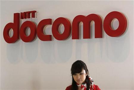 A receptionist works in front of a logo of NTT DoCoMo, Japan's biggest mobile operator, at its headquarters in Tokyo July 8, 2011. REUTERS/Yuriko Nakaj/Files