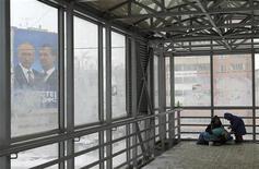 """Бездомные украваются в переходе в Казани, из окон которого виден плакат """"Единой России"""", 30 ноября 2011 года. Призывы ближайшего окружения Владимира Путина к экономическим реформам, звучавшие на старте избирательной кампании, стихли к её финишу, и даже европейский кризис не лишил власть соблазна законсервировать сырьевую модель и смириться с перспективой вялого экономического роста на долгие годы, говорят экономисты. REUTERS/Anton Golubev"""