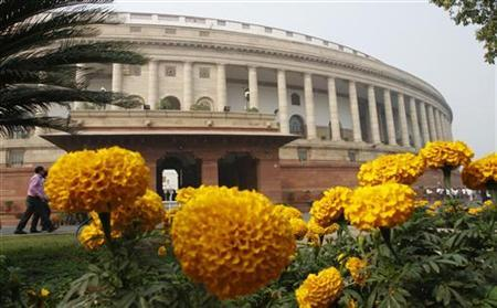 The parliament building is pictured behind marigold flowers on the opening day of the winter session of parliament in New Delhi November 22, 2011. REUTERS/B Mathur