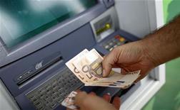 Мужчина снимает деньги с банкомата в Риме, 19 июля 2011 года. Евро стабилизировался в четверг после ралли на предыдущей сессии, вызванного действиями мировых центробанков, которые договорились совместно бороться с нехваткой ликвидности в глобальной финансовой системе. REUTERS/Max Rossi