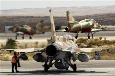 Israeli air force A-4 jets are seen in the background as personnel prepare an F-16 fighter jet at Hatzerim air base, southern Israel March 30, 2009. REUTERS/Amir Cohen