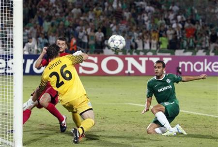Maccabi Haifa's Weaam Amasha (R) misses a shot against Racing Genk's goalkeeper Laszlo Koteles during their Champions League qualifying play-off first leg soccer match at Ramat Gan stadium near Tel Aviv August 17, 2011. REUTERS/Nir Elias/Files