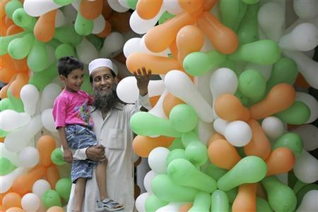 A man shows balloons in the colours of the Indian flag to his child at a market during Independence Day celebrations in Chandigarh August 15, 2008. REUTERS/Ajay Verma/Files