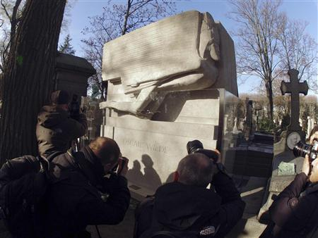 Photographers take pictures of the renovated tomb of Oscar Wilde during the ceremony at the Pere Lachaise cemetery in Paris November 30, 2011. REUTERS/Charles Platiau