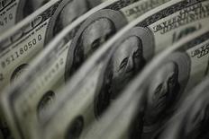 Долларовые купюры в Токио 2 августа 2011 года. Второй по выручке российский продуктовый ритейлер Магнит закрыл книгу заявок SPO, определив цену акции в $85, что позволит ему привлечь $350 миллионов, сообщила компания в пятницу. REUTERS/Yuriko Nakao