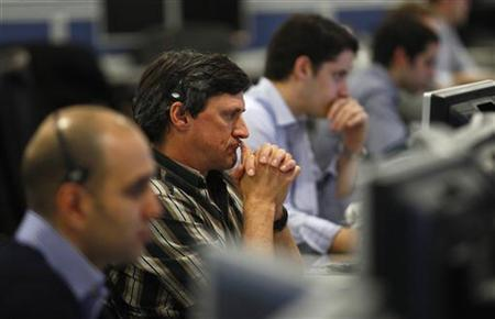 Traders at IG Index look at their screens at their offices in the City of London March 15, 2011. REUTERS/Andrew Winning/Files