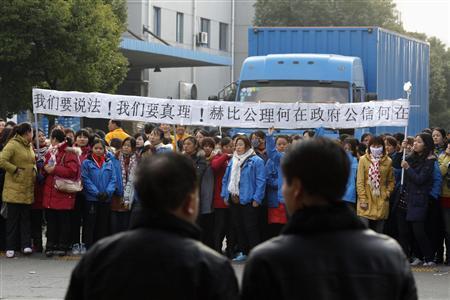 Two men watch as workers on strike block the entrance gate of Hi-P International factory in Shanghai December 2, 2011.  REUTERS/Carlos Barria
