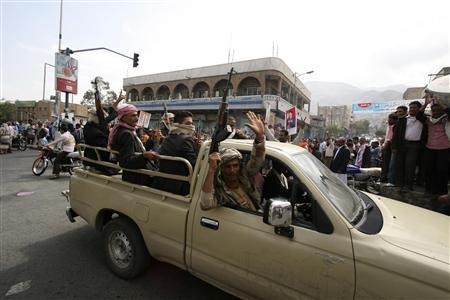 Opposition fighters patrol a street during clashes with government forces in the southern Yemeni city of Taiz December 1, 2011.  REUTERS/ Stringer