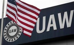 Американский флаг на фоне логотипа Объединенного профсоюза работников автомобильной промышленности, 8 сентября 2011 г.  Рост занятости в США ускорился в ноябре, а уровень безработицы упал до минимума двух с половиной лет - 8,6 процента, подтвердив, что экономическое восстановление набирает темпы. REUTERS/Rebecca Cook
