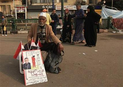 A man sits in front of a poster that reads ''Penalty for murderers of martyrs'' in Tahrir Square, Cairo November 30, 2011. REUTERS/Esam Al-Fetori