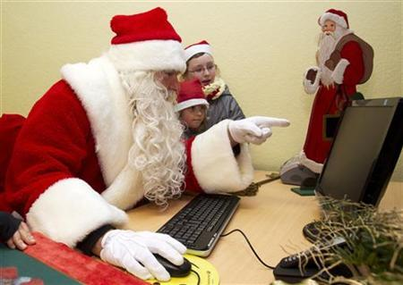 A man dressed as Father Christmas and children look at a computer screen at a special Christmas post office in the village of Himmelpfort (Heaven's Gate), north of Berlin November 10, 2011.  REUTERS/Thomas Peter