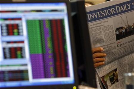 An Indonesian broker reads a newspaper near his monitor at Bank Mandiri Sekuritas trading floor in Jakarta August 8, 2011. REUTERS/Beawiharta