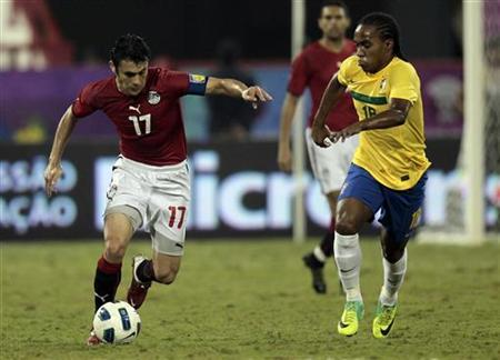 Brazil's Willian Da Silva (R) fights for the ball with Egypt's Ahmed Hassan during their international friendly match in Doha November 14, 2011. REUTERS/Fadi Al-Assaad