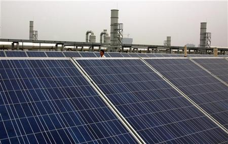 A worker walks behind solar panels on the factory roof of Yingli Green Energy Holding Company, also known as Yingli Solar, located in the city of Baoding, Hebei Province June 20, 2011. REUTERS/David Gray