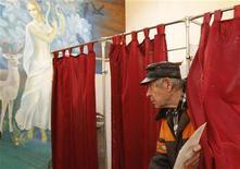 Мужчина голосует на выборах в Госдуму РФ в Вороново, в 60 километрах к югу от Москвы, 4 декабря 2011 года. Россия в воскресенье голосует на выборах в Госдуму, которые правящая верхушка рассматривает как вотум о доверии курсу вновь метящего в президенты премьера Владимира Путина, а оппоненты - как предпоследний шанс пошатнуть его десятилетнюю политическую монополию ненасильственными методами. REUTERS/Denis Sinyakov  (RUSSIA - Tags: POLITICS ELECTIONS)